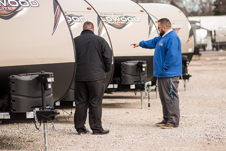 All American Coach / RV Wholesale Superstore employee shows customer a travel trailer on the lot.