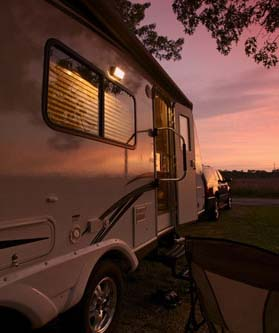 Luxury travel trailer parks on grass as sun sets