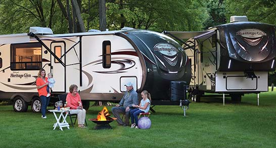 Family sits outside in front of two RVs and learns about travel trailers